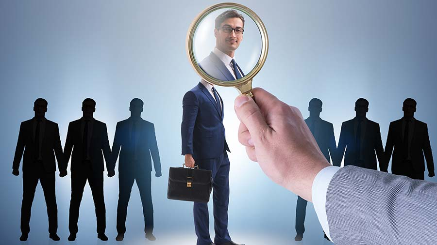 Magnifying glass hovering over potential employee to show the screening process