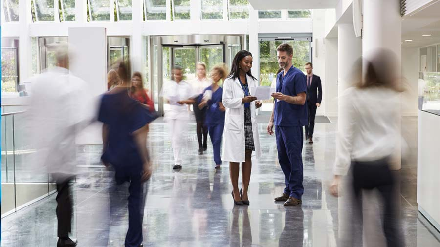 A doctor and a nurse talking in the hospital lobby